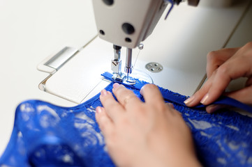 Hands of a woman sewing blue fabric