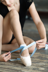 Girl tying her ballet shoes