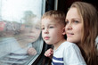 Mother and son looking through a train window