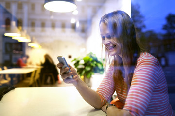 Young woman sitting in a restaurant using a mobile
