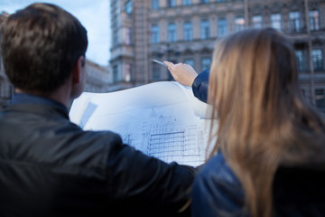 Man and woman holding blueprint