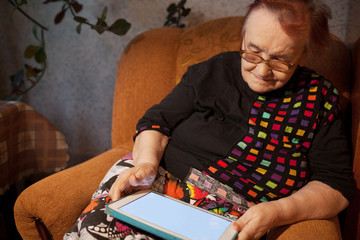 Elderly lady sitting in an chair using a tablet