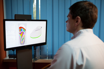 Orthopaedist at work with digital footstep model