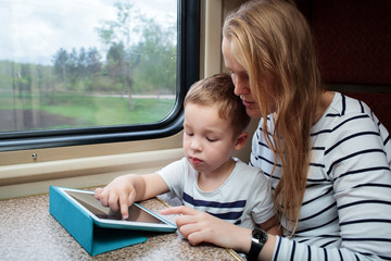 Son and his mom with tablet PC in the train