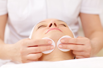 Cosmetician cleaning face using cotton pads