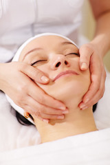 Woman in the beauty spa getting a facial massage