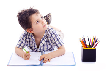 Schoolboy drawing with colored pencils, isolated on white backgr