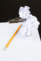 Crumpled paper balls with pencil and clipboard
