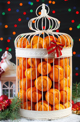 Tangerines in decorative cage with Christmas decor,