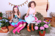 Beautiful small girls in petty skirts holding watering cans