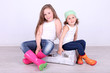 Beautiful small girls sitting on suitcase on wall background