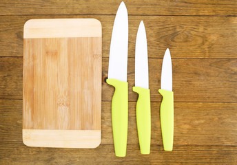 Kitchen knives and cutting board on wooden table