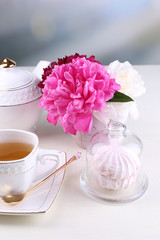 Composition of beautiful peonies in vase, tea in cup and