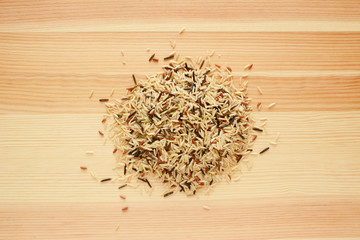 Wild rice, brown basmati and red camargue grains on wood