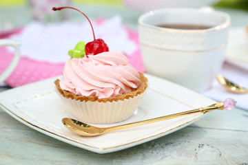 Tasty cake and cup with tea on table, close-up, outdoors