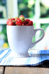 Forest berries in cup, on wooden table, on bright background