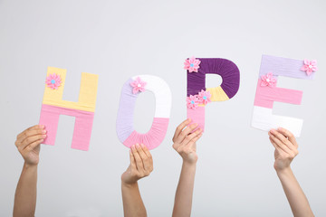 Hands holding up letters building word hope on grey background