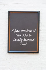 Isolated noticeboard for a pub on a white painted brick wall