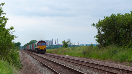 Freight train with cargo containers passing through countryside