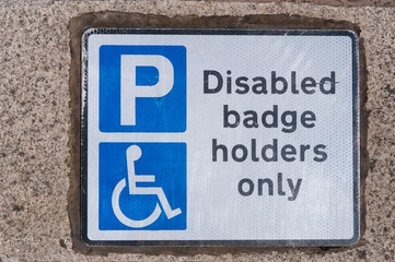 Disabled badge holders only sign on concrete