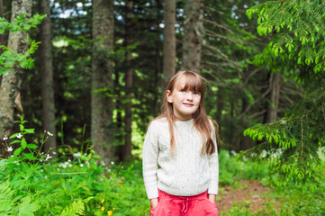 Outdoor portrait of a cute little girl in a forest