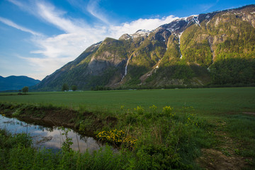 Norway in May. Flowering fields and waterfalls in the mountains