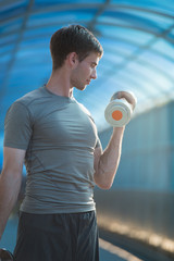 Athletic man doing exercises dumbbells