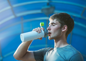 Athletic young man drinking water