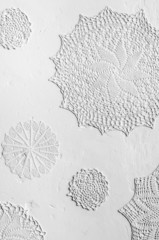 crocheted doilies in gesso on a wall