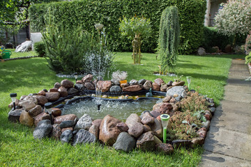 fountain in a beautiful garden with plants