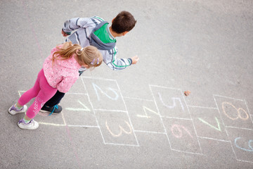 Brother and sister play hopscotch