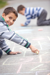 Cute little boy drawing with chalk outdoors