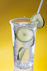 Mineral Water With Llime in a Plastic Cup on a Yellow Background