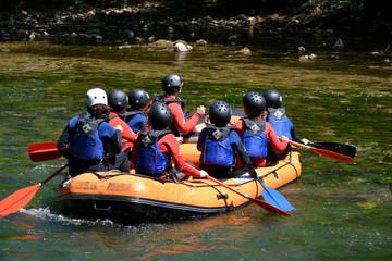 grupo de niños practicando rafting en verano