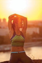 Young woman stretching outdoor in the sunset
