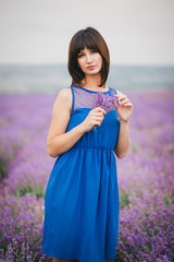 Woman with a bouquet of lavender standing in a lavender field