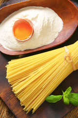 Dried spaghetti and scoop of flour with fresh egg