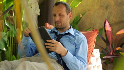 Businessman with tablet computer at luxury gazebo in garden