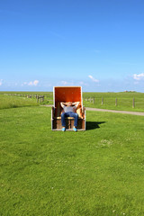 Relaxed man enjoys on a beach chair on the Hallig Langeneß