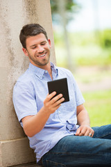 Young man reading E-book outside