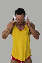 Muscular man standing, listening to music on headphones