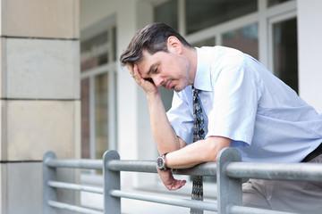 verzweifelter Manager an einem Geländer