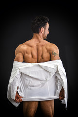 Male bodybuilder undressing revealing muscular back