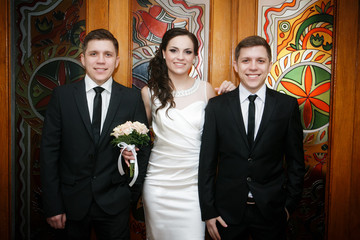 groom with the bride and the brother  of the twin