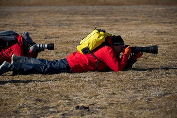 Two photographers with cameras lying on ground