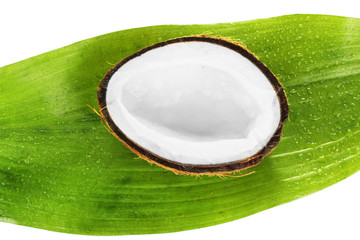 half coconut with green leaf on white background close-up