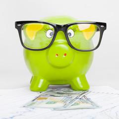 Green piggy bank with 100 dollars banknote - 1 to 1 ratio