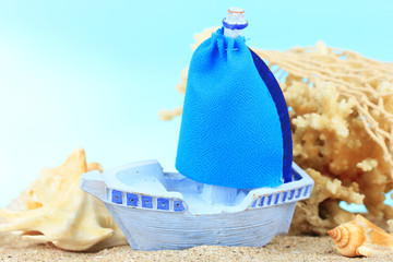 Blue toy ship on sand, on blue background