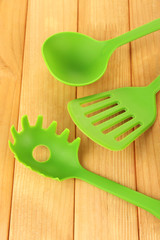 Plastic kitchen utensils on wooden background