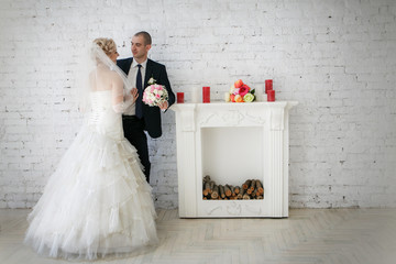 beautiful bride an groom on their wedding day near fireplace